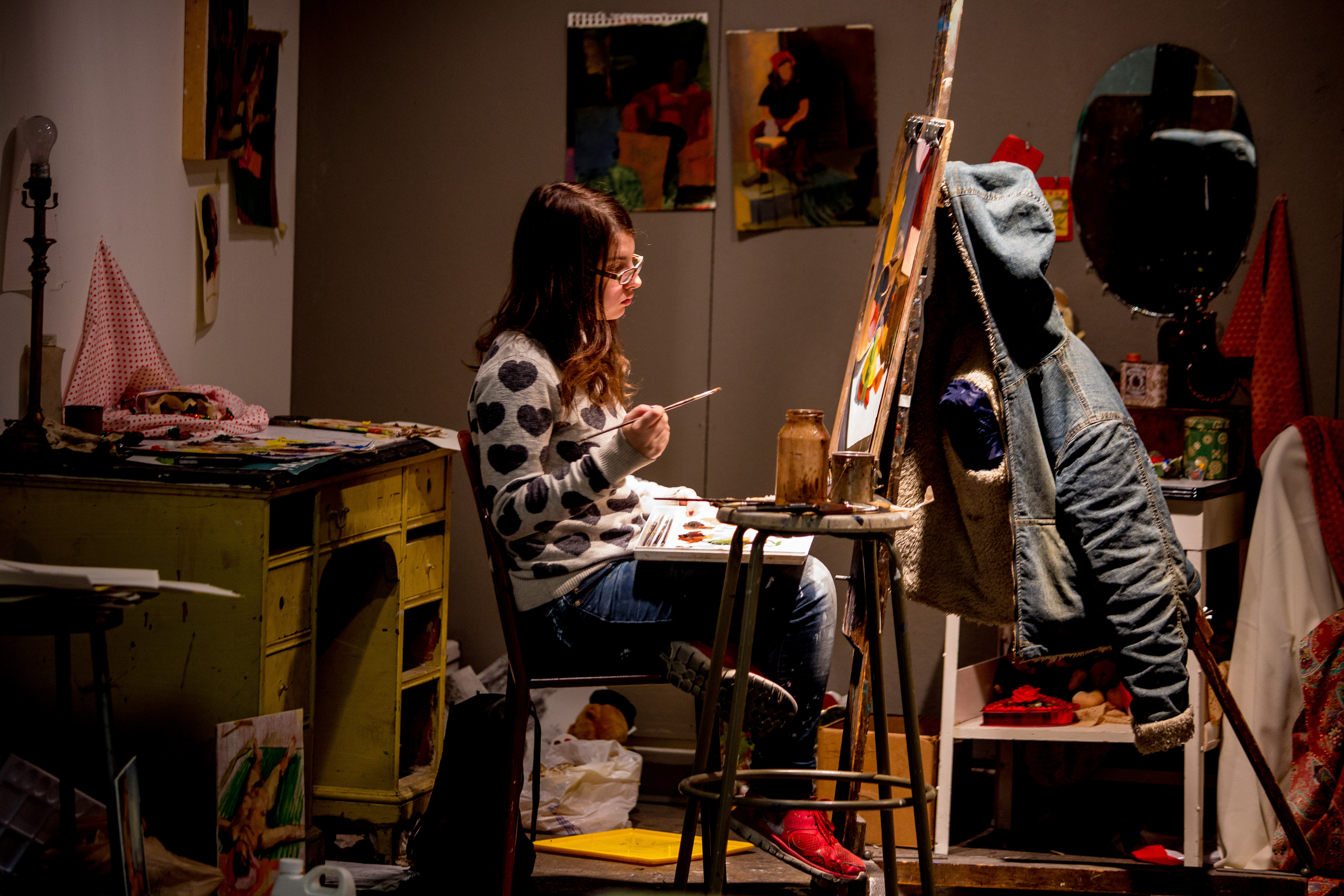 A student works on their painting in their private studio space.