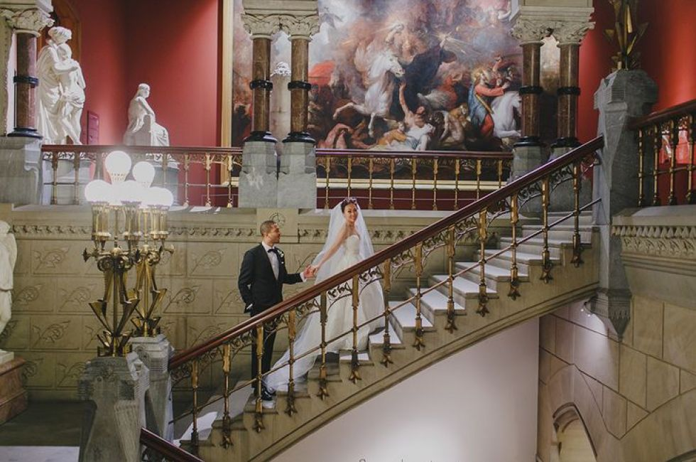 Bride and groom on the staircase of the Historic Landmark Building.