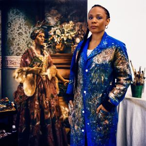 Image of the artist with her paintings, photo from Vogue magazine (Photographed by Anton Corbijn, Vogue, October 2018 / Painting: Elizabeth Colomba. Winter, 2017. Oil)