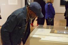 One person in a hat looking at an exhibit under glass