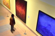 One person standing in front of three paintings on a wall