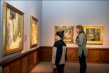 Two people looking at the paintings in the gallery