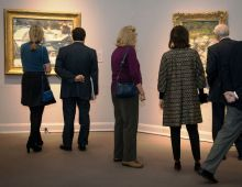 Five people looking at the paintings on the wall