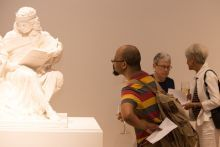 Three people looking at a sculpture