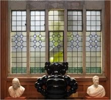 KAWS, interior view with BORN TO BEND seen through stained glass window in Washington Foyer, Historic Landmark Building, PAFA