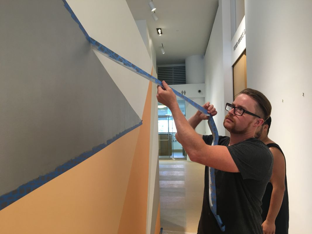 Matt Chapman (MFA '15) works on the temporary mural in the Hamilton Building.