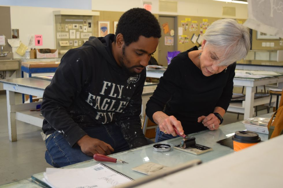 Lamar, a program participant, works in the print shop with PAFA alum Christine Stoughton