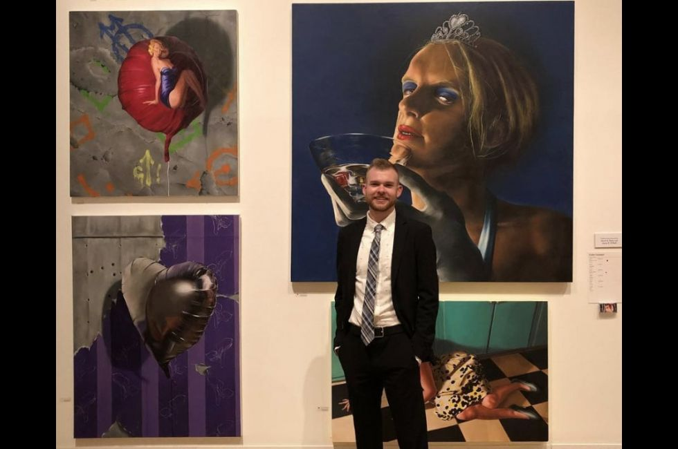 collin cousart stands in front of his work at the ASE