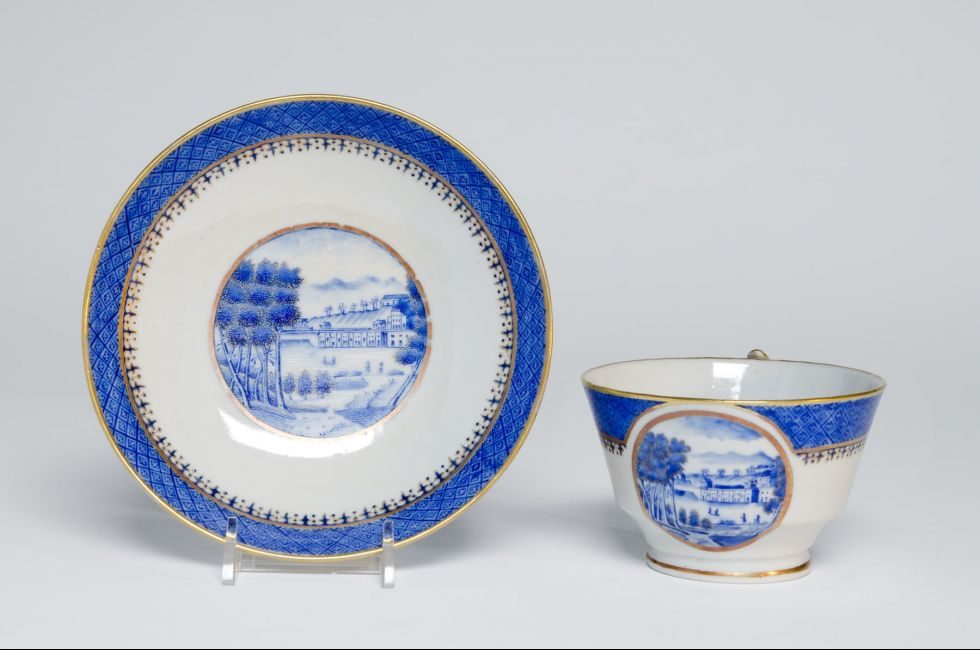 "Artist/maker unknown, Chinese, for export to the American market, "" Cup and saucer showing the Philadelphia Waterworks"" (1825). Hard-paste porcelain with cobalt underglaze, decoration, and gilt. Cup: 2 5/8 x 4 3/8 x 3 5/8 in.; saucer: 1 1/8 x 5 1/2 in. 