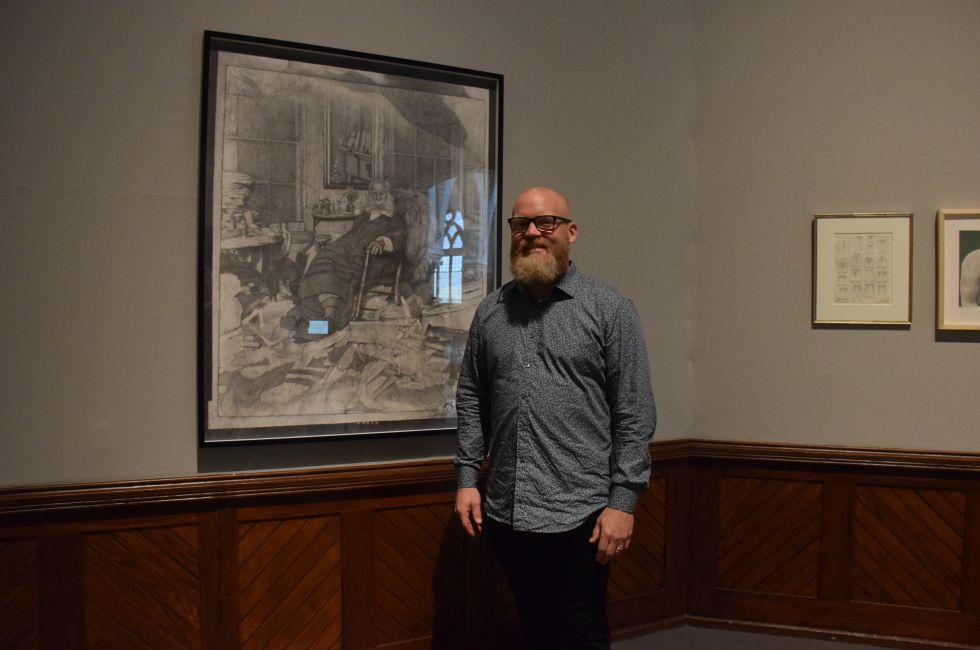 "Artist Mark Stockton stands in front of his work, ""The Poet in His Bedroom..."" at the opening reception for the Youth Council's exhibition, ""Multitudes: Whitman at 200."""