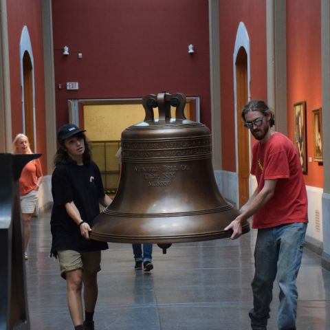 Alumni Erin Addie '18 and Gary Pergolini '18 move the replica Justice Bell into the Rotunda of the Historic Landmark Building.