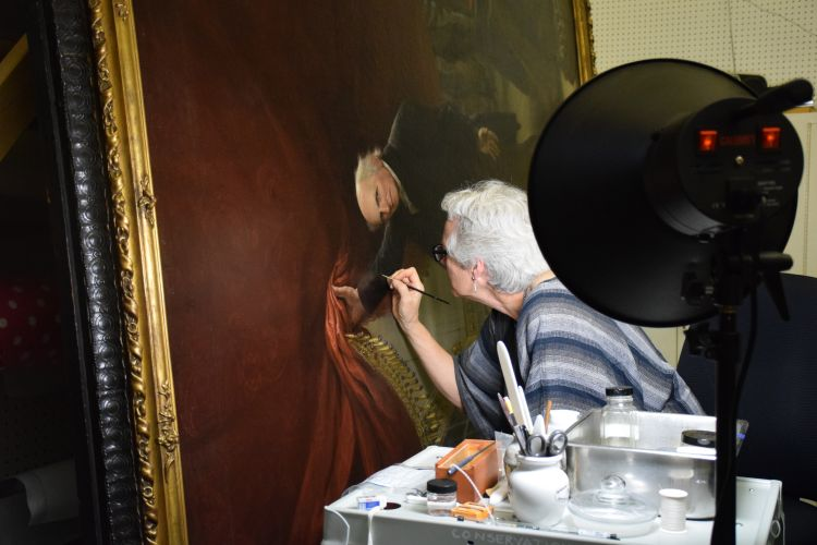 Mary McGinn, PAFA's Paintings Conservator, working on Charles Wilson Peale's The Artist in His Museum.
